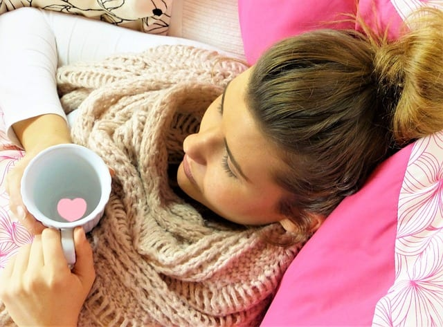 Colds and Flu: What's the Difference? A sick woman holding a cup of tea.